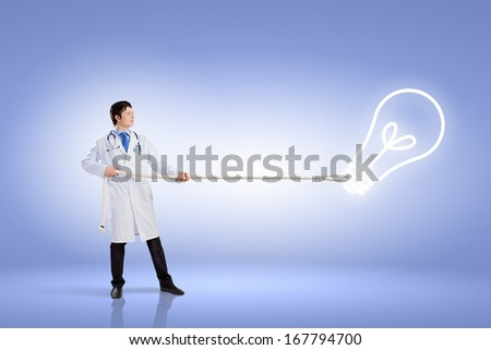 Image of male doctor pulling idea sign with rope - stock photo
