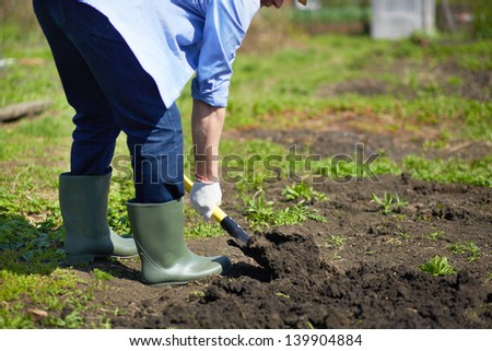Image of male farmer didgging in the garden - stock photo
