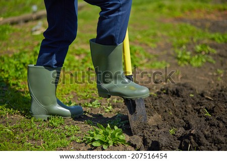 Image of male farmer digging in the garden - stock photo