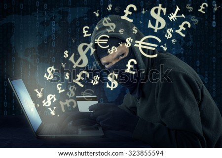 Image of male hacker wearing mask and using laptop while holding credit card to steal money through online transaction - stock photo