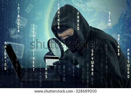Image of male hacker wearing mask and using magnifying glass to see the credit card number - stock photo