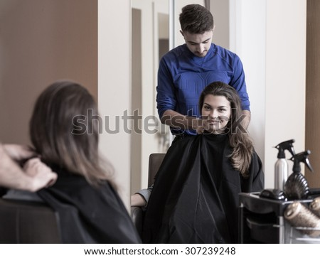 Image of male hairdresser and attractive woman - stock photo