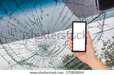 image of male hand holding smart phone with blank white screen and Broken car windshield take photo from inside from accident of car.  - stock photo