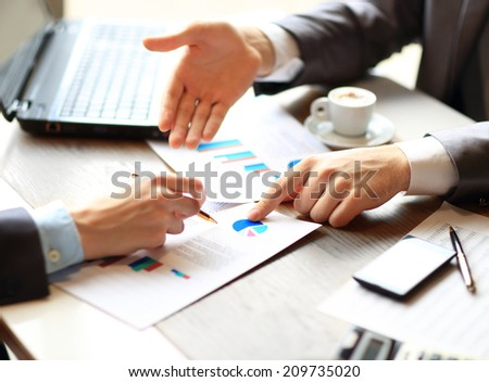 Image of male hand pointing at business document during discussion at meeting