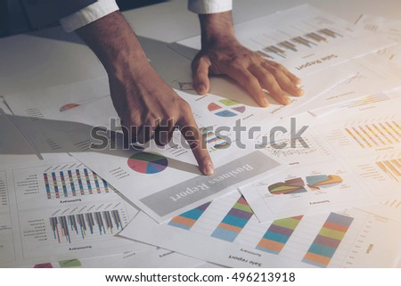 Image of male hand pointing at business report document