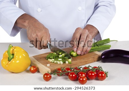 Image of male hand with knife cutting vegetables on wooden board