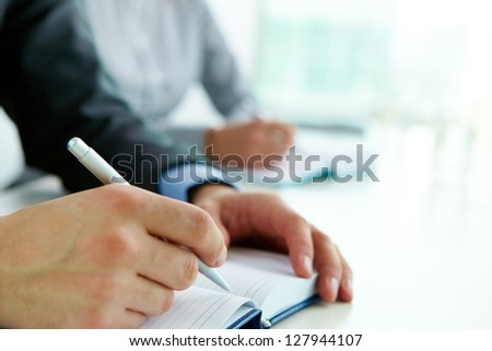 Image of male hand with pen over open notebook at seminar