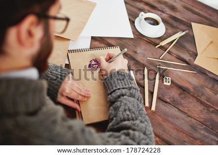 Image of male hands over notepad drawing pictures with different art objects near by - stock photo