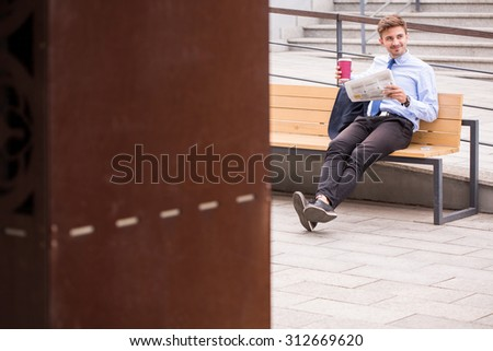 Image of male passenger drinking coffee on train station - stock photo