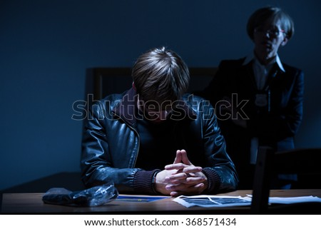 Image of male suspect with head down on police station - stock photo