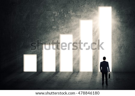 Image of male worker standing in front of rising financial graph while holding a briefcase