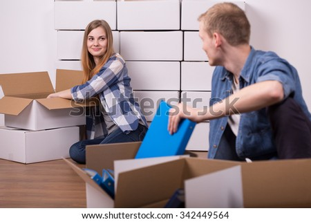 Image of man and woman packing things into cardboard boxes