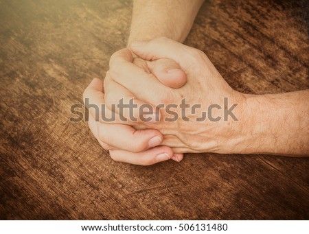 Image of  man hands praying to God on wooden table  in the dark room with the light from above, vignette and vintage color effected, Conceptual image, Christian Background with copy space