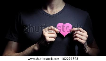 Image of man holding paper heart cutout - stock photo