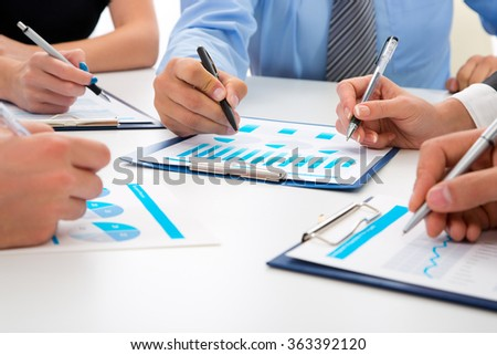 Image of man's hand pointing at business document during discussion at meeting