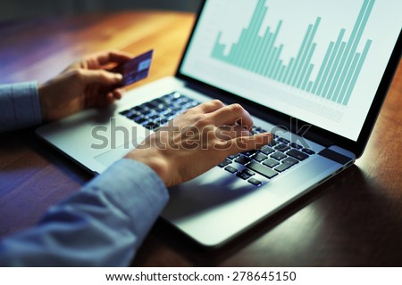 Image of man's hands with credit card over laptop working with data graph on screen. Selective focus - stock photo