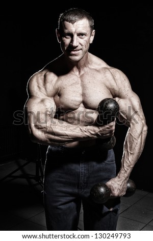 Image of man with big and muscular hands standing with a dumbbells