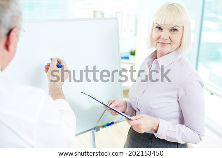 Image of mature businesswoman looking at camera while her partner making presentation on whiteboard near by