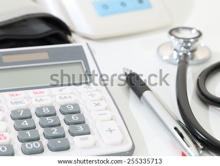 image of medical calculator stethoscope pen and blood pressure on white desk