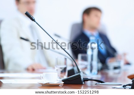 Image of microphone standing on table at conference against defocused background of two businessmen - stock photo