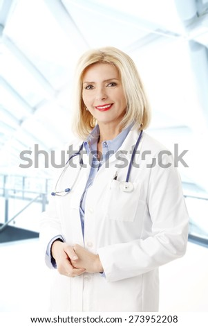 Image of middle age smiling female doctor with stethoscope standing at hospital. Medical occupation. - stock photo