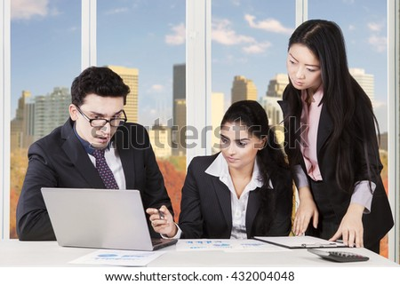 Image of middle eastern businessman speaking with indian and chinese businesswomen at the workplace - stock photo