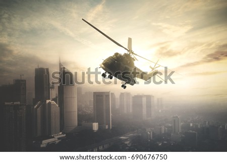 Image of military helicopter is flying over downtown while doing patrols, shot at sunrise time