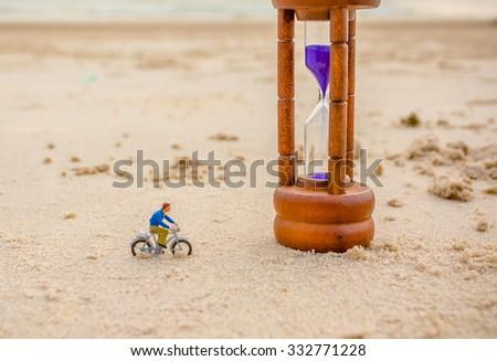 image of mini figure dolls biker and sandglass on the beach blur in background. - stock photo