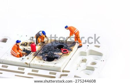 image of mini figure dolls engineer fix Burned plug socket isolated on white background. - stock photo