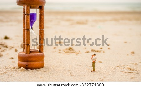 image of mini figure dolls photographer take picture on sandglass on the beach blur in background. - stock photo