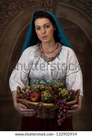 Image of model dressed in old world clothing carrying a basket of fruit - recreating old paintings of years gone by but with photography - stock photo