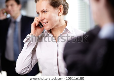 Image of modern businesswoman with cellular phone in working environment - stock photo