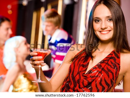 Image of modern woman holding glass of martini and looking at camera with smile