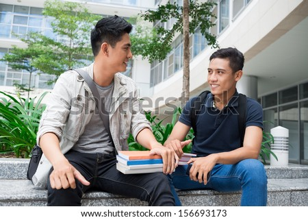 Image of modern young student sitting with books and talking outside