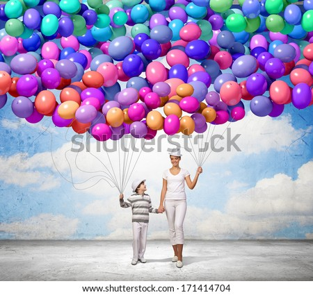 Image of mother and son holding bunch of colorful balloons - stock photo