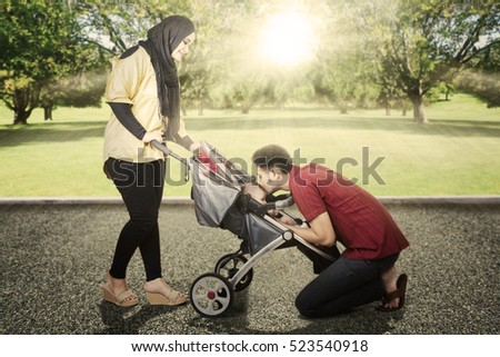 Image of mother holding carriage while looking at her husband kissing their baby in the park
