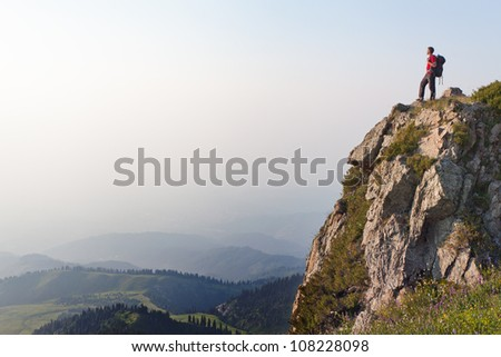 Image of mountain scenery, on top of which stands the silhouette of a tourist, who looking into the valley. - stock photo