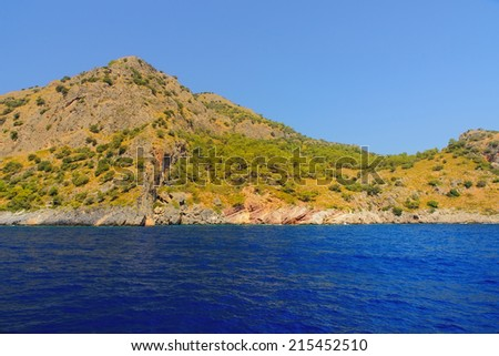 Image of mountains and hills with a deep blue sea in the foreground and blue skies overhead, with room for copy space. Taken from a boat cruise in Olu Deniz in Turkey - stock photo