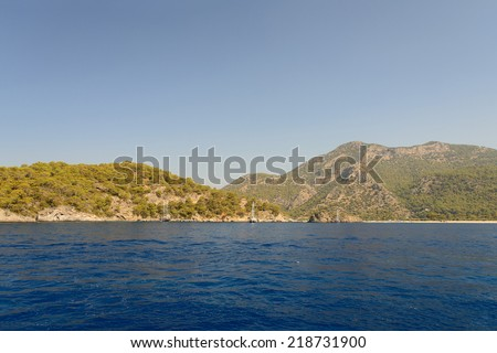 Image of mountains and hills with a deep blue sea in the foreground and blue skies overhead, with room for copy space. Taken from a cruise in Olu Deniz on the turquoise coast of south-western turkey - stock photo