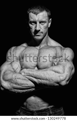 Image of muscle man who is posing on the black background - stock photo