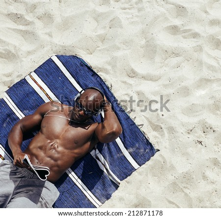 Image of muscular young man lying on a mat reading magazine. Shirtless male model relaxing on beach. - stock photo