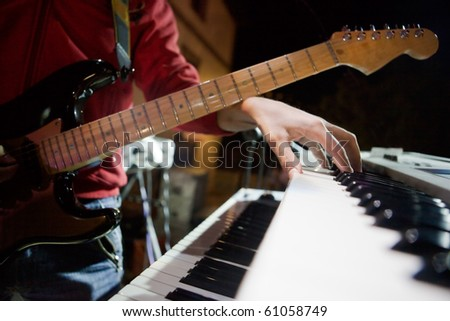 image of musician with guitar and keys live - stock photo