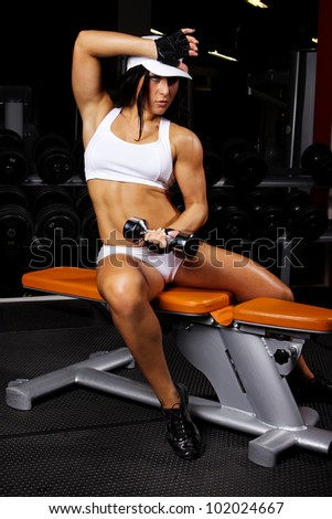 Image of musle woman doing exercises in gym with dumbbels