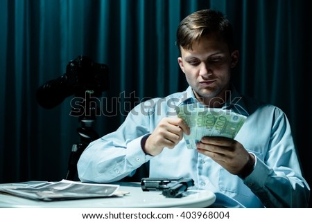 Image of mysterious man with money and his illegal profession - stock photo