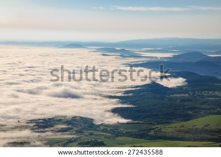 Image of mystical fog in the valley from above. - stock photo