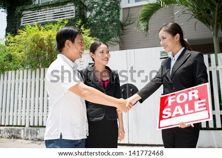 Image of new owners coming to an agreement with a realtor - stock photo