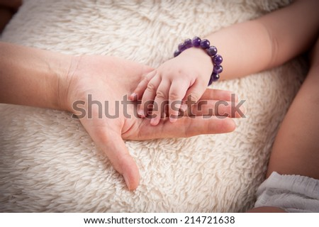 Image of newborn baby hand over female palm