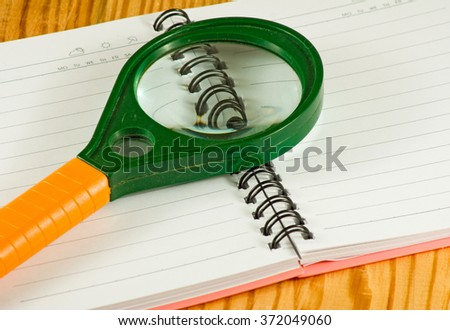 image of notebook and magnifying glass on a table closeup - stock photo