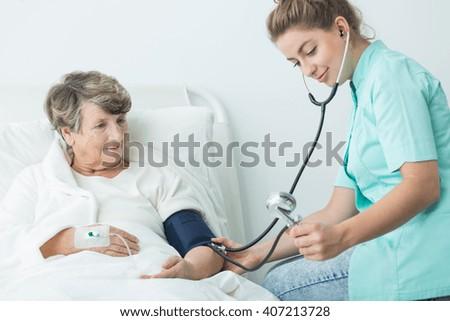 Image of nurse take care of senior hospital patient - stock photo