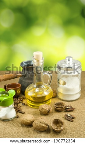 image of nuts, butter, salt shaker, coffee beans, a cup on a green background - stock photo